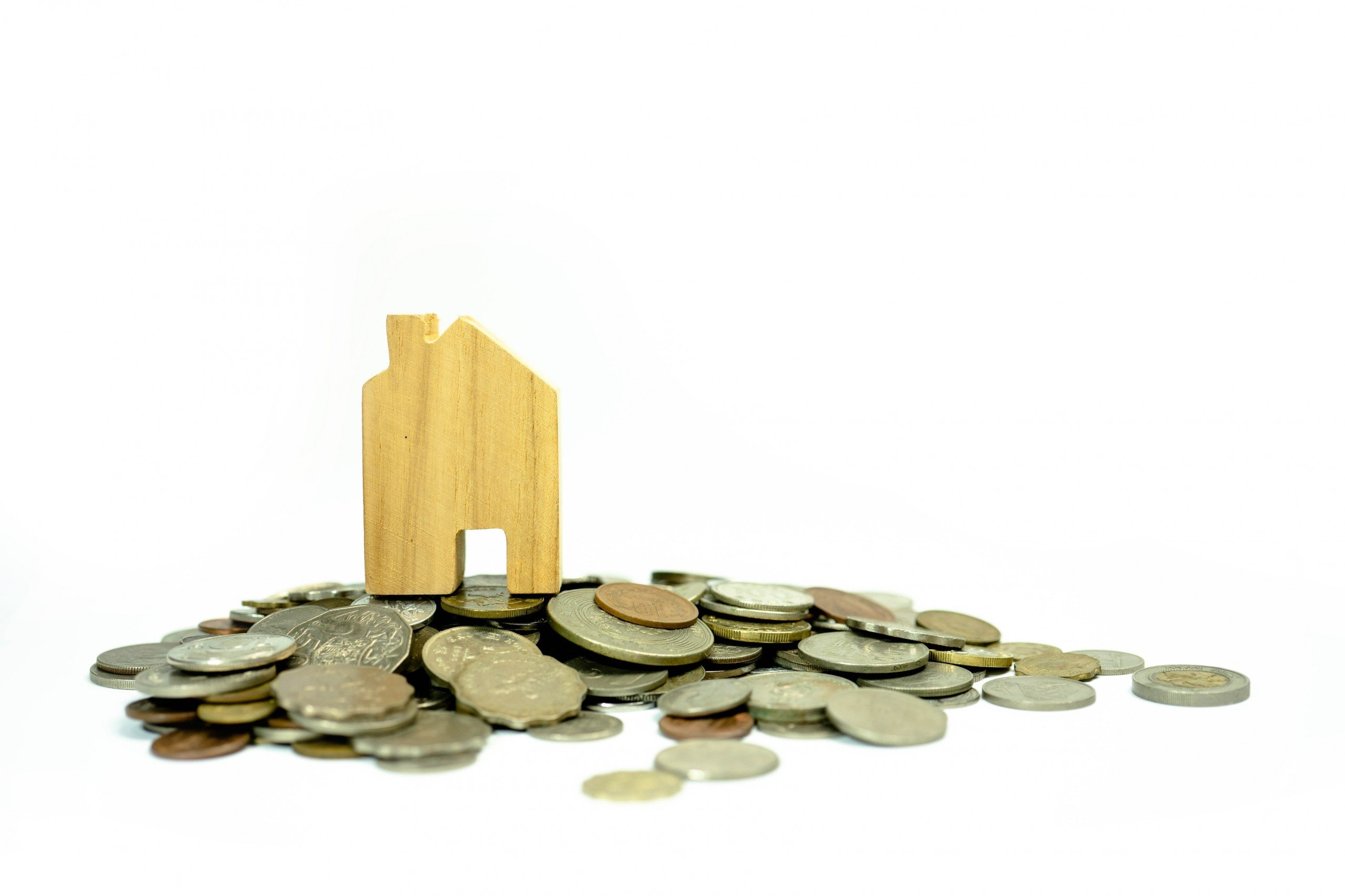 Wooden house with many coins by its feet